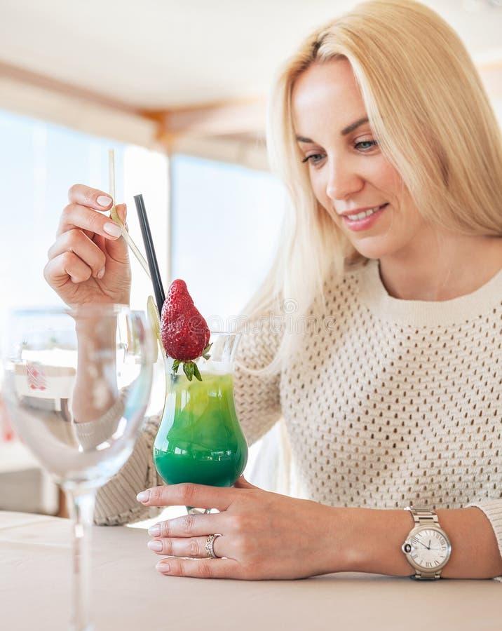 Nätt kvinna i kafé med den ljusa tropiska coctailen Lokal fokus royaltyfria foton