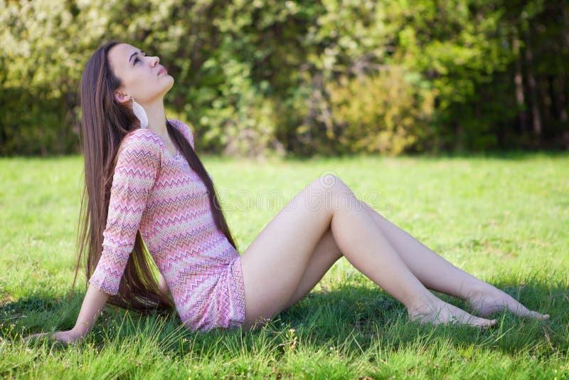 Nätt kvinna i parkerasammanträdet på gräs royaltyfri fotografi