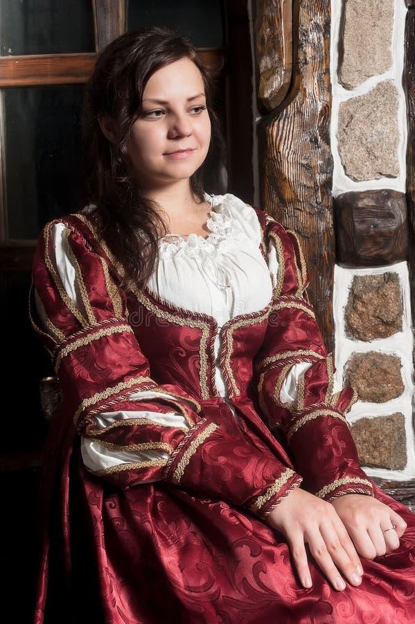 Nätt kvinna i röd klänning i retro barock stil royaltyfri foto