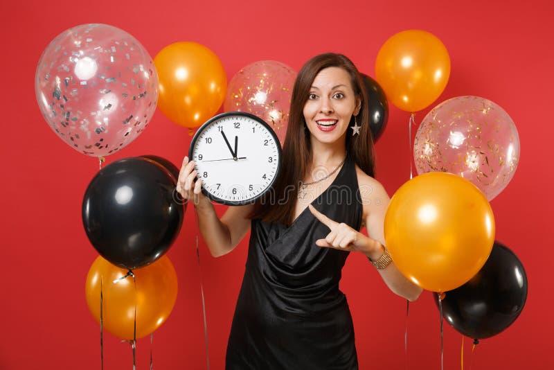 Nätt kvinna i svart klänning som firar peka pekfingret på den runda klockan i händer på ljus röd bakgrundsluft arkivbild