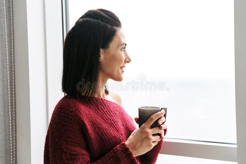 Nätt kvinna inomhus i hem nära fönstret som dricker kaffe fotografering för bildbyråer