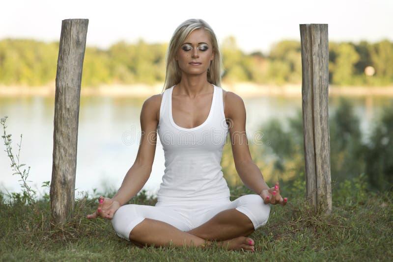 Nätt kvinna Lotus Pose Outdoors arkivbilder