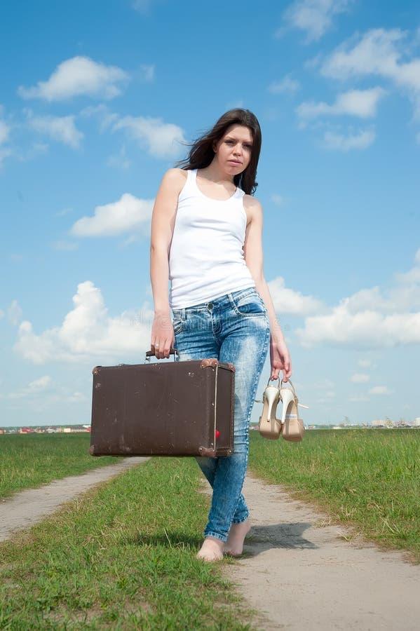 Nätt kvinna med den gamla resväskan arkivbild