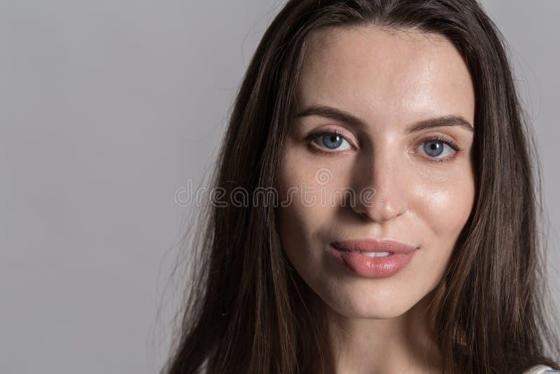 Nätt kvinna med fluffigt hår, påklädd tillfälligt mot en grå studiovägg royaltyfri bild