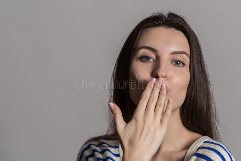Nätt kvinna med fluffigt hår, påklädd tillfälligt mot en grå studiovägg royaltyfri foto