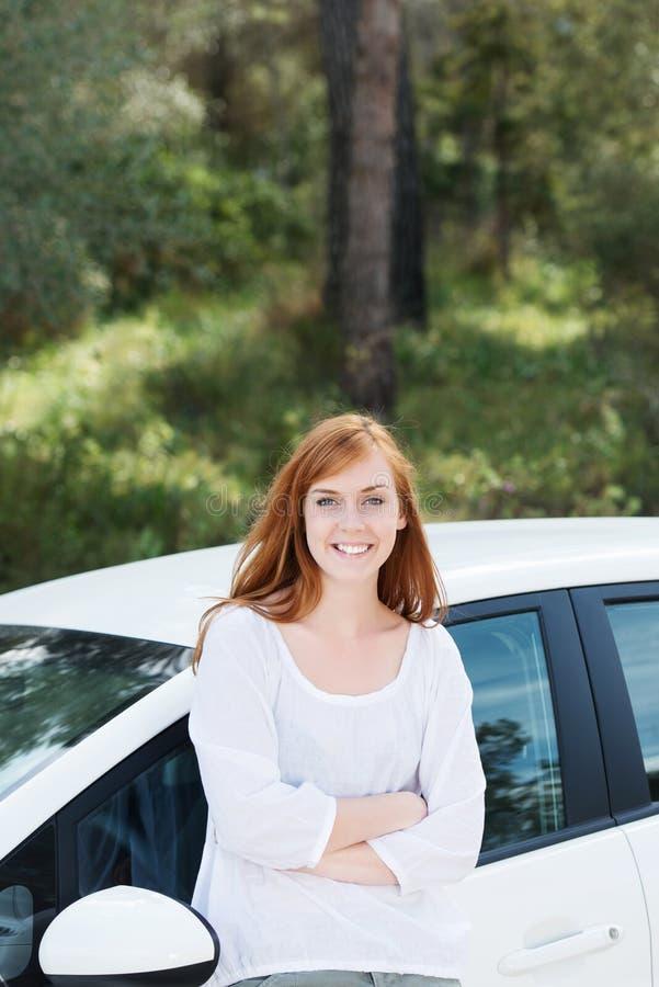 Nätt kvinna med hennes nya bil royaltyfria bilder