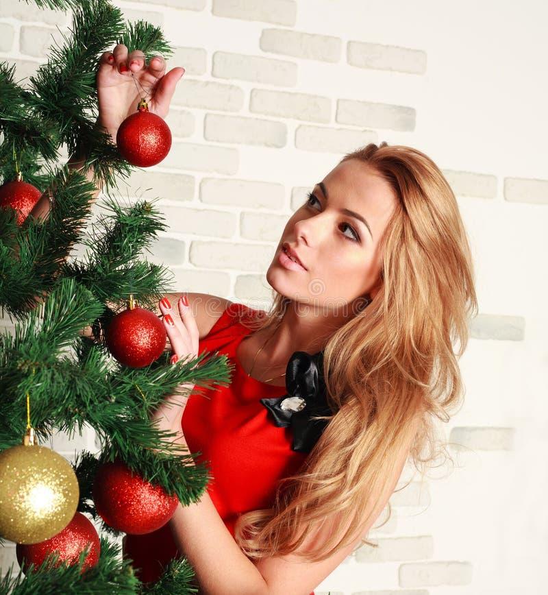 Nätt kvinna med julträdet arkivbild