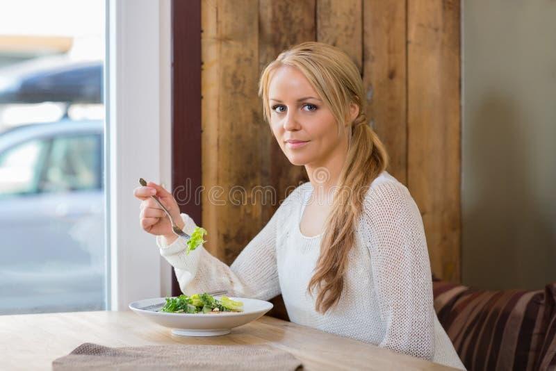 Nätt kvinna med plattan av sallad i kafé royaltyfria foton