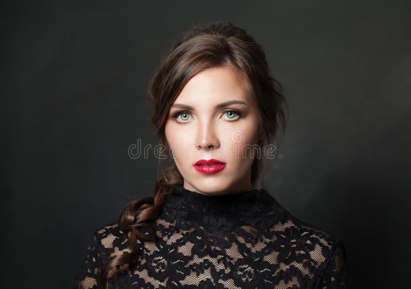 Nätt kvinna med rött kantmakeuphår på svart bakgrund royaltyfria foton