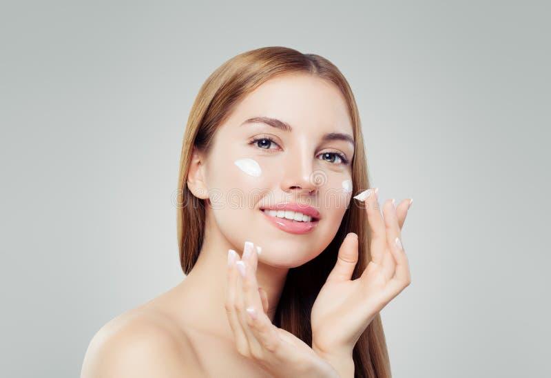 Nätt kvinna med sund hud som applicerar anti--åldras kräm och att le Flå omsorg, skönhet och det ansikts- behandlingbegreppet royaltyfria bilder