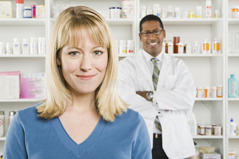 Nätt kvinna och apotekare At Pharmacy arkivfoto