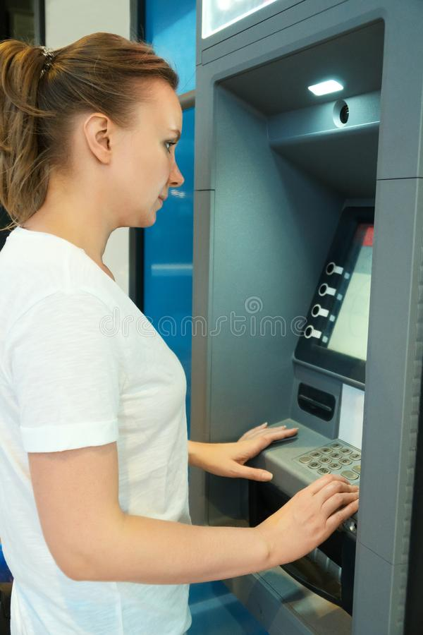 Nätt kvinna som använder ATM arkivbilder