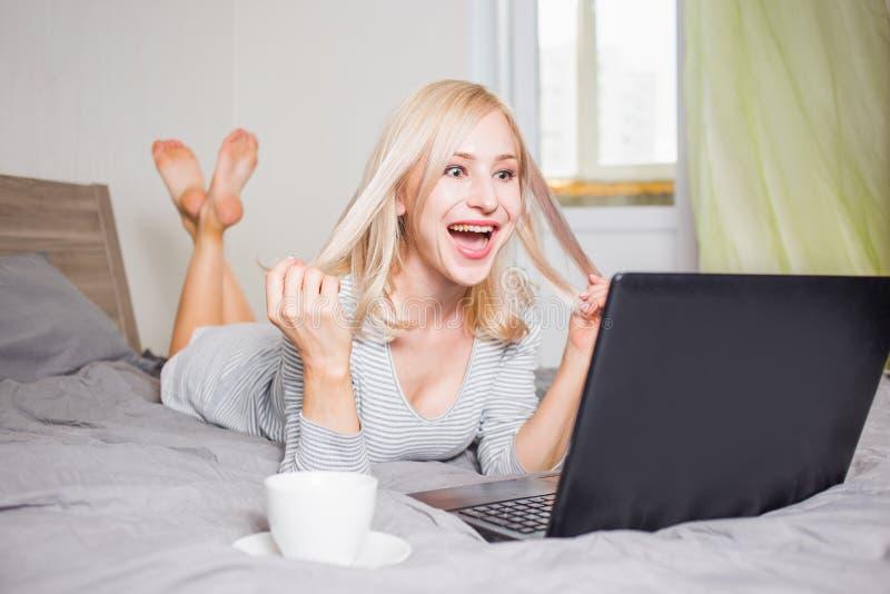Nätt kvinna som använder bärbara datorn, medan ha en kopp kaffe på säng royaltyfria foton