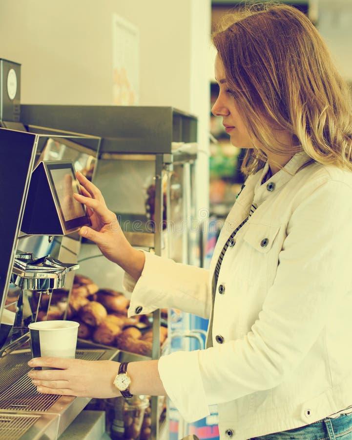 Nätt kvinna som använder kaffevaruautomaten arkivfoton