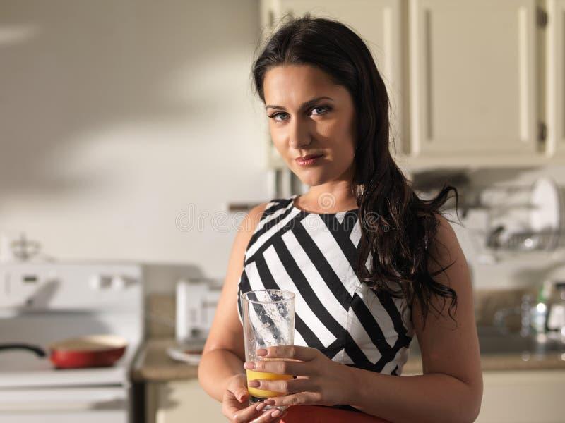 Nätt kvinna som bär den retro klänningen och rymmer exponeringsglas av orange fruktsaft i kök arkivfoton