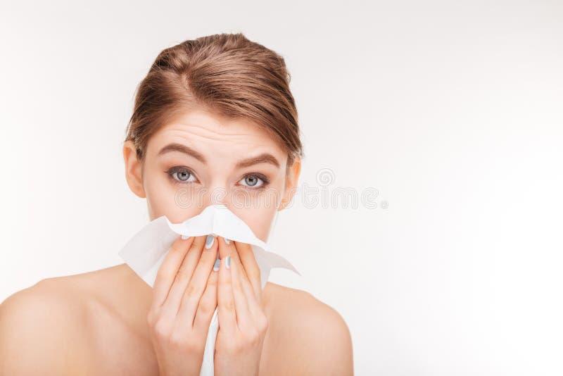 Nätt kvinna som blåser näsan och använder den pappers- näsduken arkivbilder