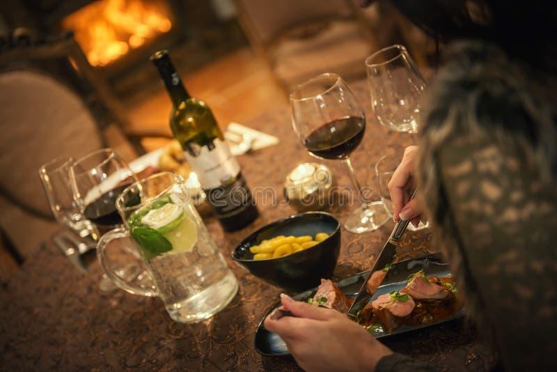 Nätt kvinna som dricker rött vin och äter i restaurangen, vintertid, romantisk matställe royaltyfria foton