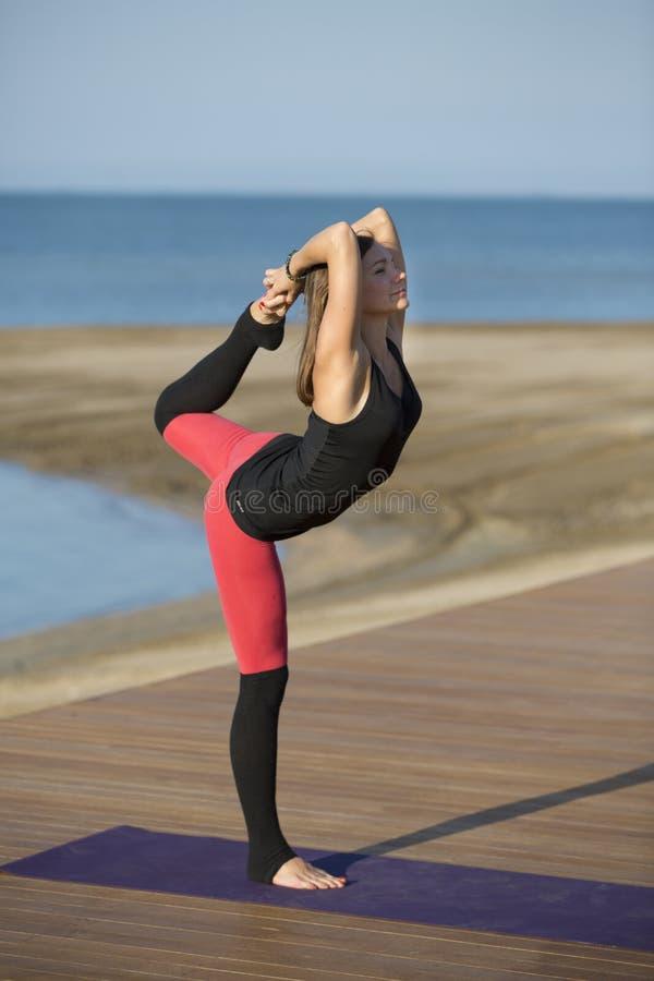 Nätt kvinna som gör yoga på stranden fotografering för bildbyråer