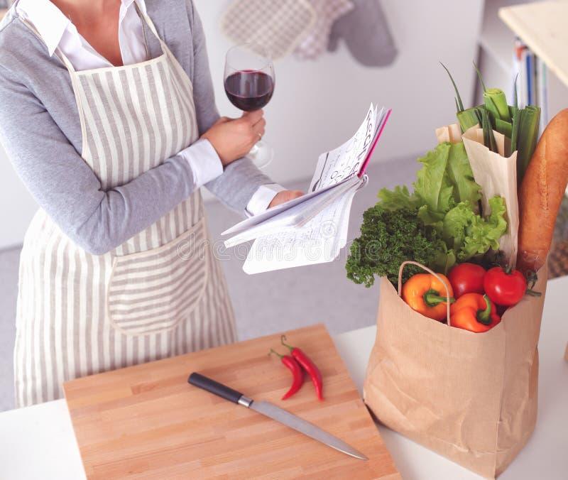 Nätt kvinna som hemma lagar mat och dricker något vin i kök royaltyfri foto