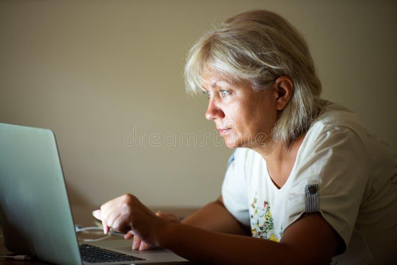 Nätt kvinna som ikväll ser på anteckningsboken royaltyfri foto