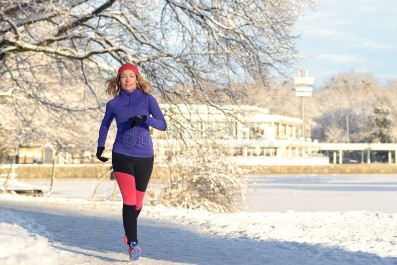 Nätt kvinna som joggar i vinter med hörlurar arkivfoton