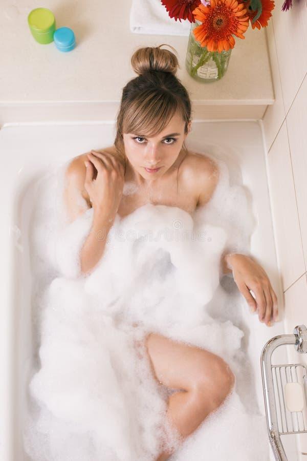 nätt kvinna som kopplar av i badrum arkivfoto
