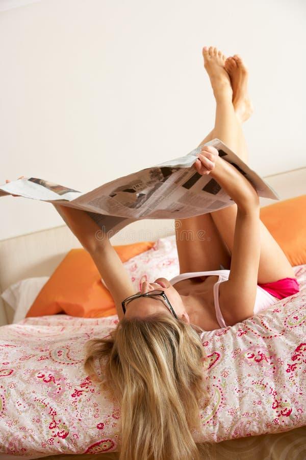 Nätt kvinna som kopplar av på sängläsningtidningen fotografering för bildbyråer