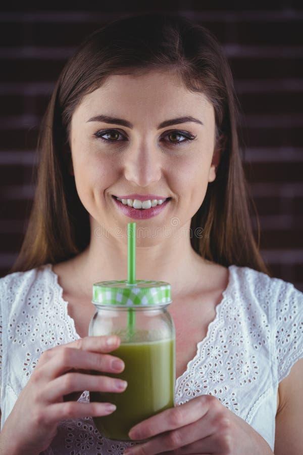 Nätt kvinna som läppjar på grön fruktsaft arkivfoton