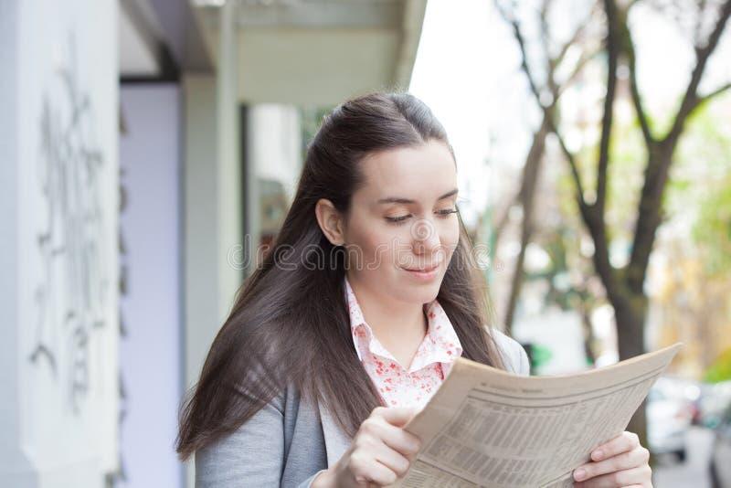 Nätt kvinna som läser en tidning i gatan arkivbild