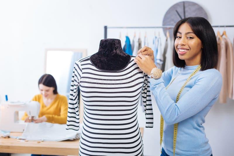 Nätt kvinna som ler, medan stå med hennes händer som trycker på skyltdockan arkivfoton