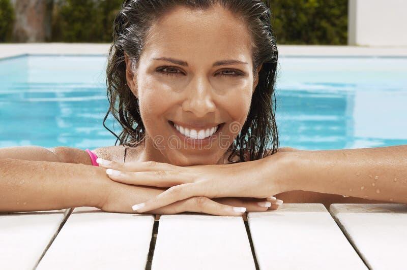 Nätt kvinna som ler på poolsiden fotografering för bildbyråer