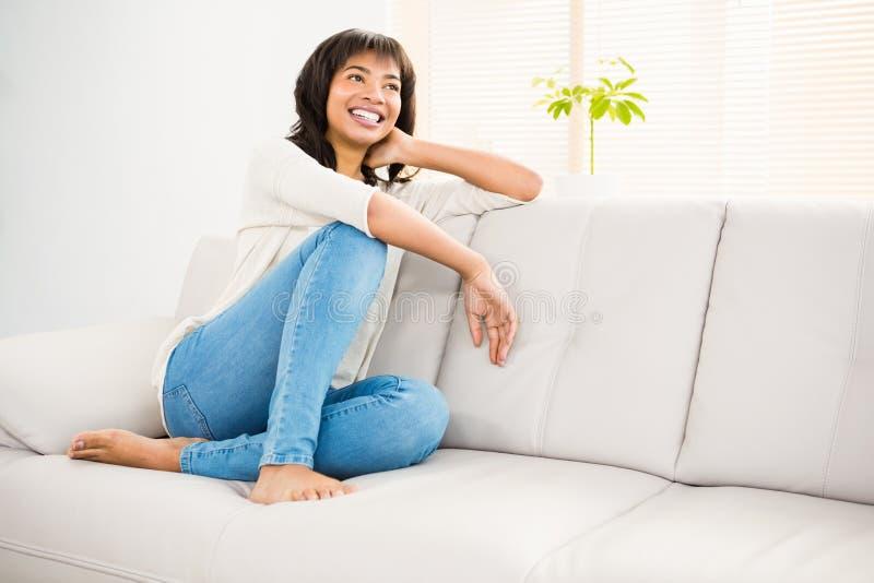 Nätt kvinna som ler på soffan royaltyfri bild