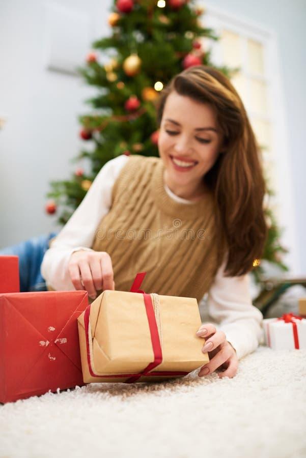 Nätt kvinna som packar upp julklapp arkivbilder