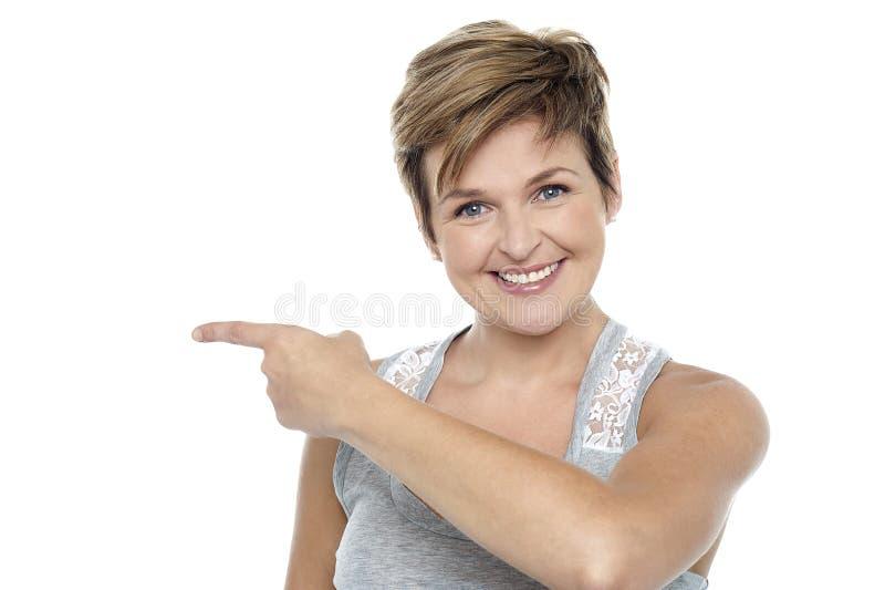 Nätt kvinna som pekar in mot kopieringsavståndsområde royaltyfria foton