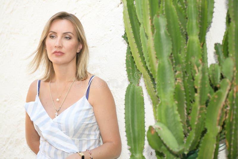 Nätt kvinna som poserar på en vit vägg som dagdrömmer med en stor grön kaktus på sidan royaltyfri foto