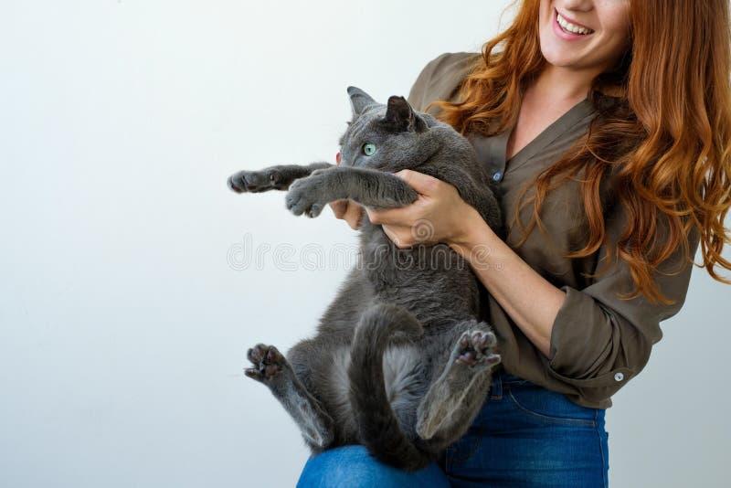 Nätt kvinna som rymmer hennes blåa katt för ryss i händer royaltyfria foton