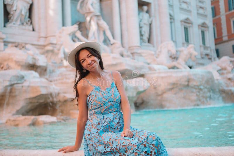 Nätt kvinna som ser till springbrunnen av Trevi under hennes tur i Rome, Italien Flickan tycker om hennes europeiska semester royaltyfria foton