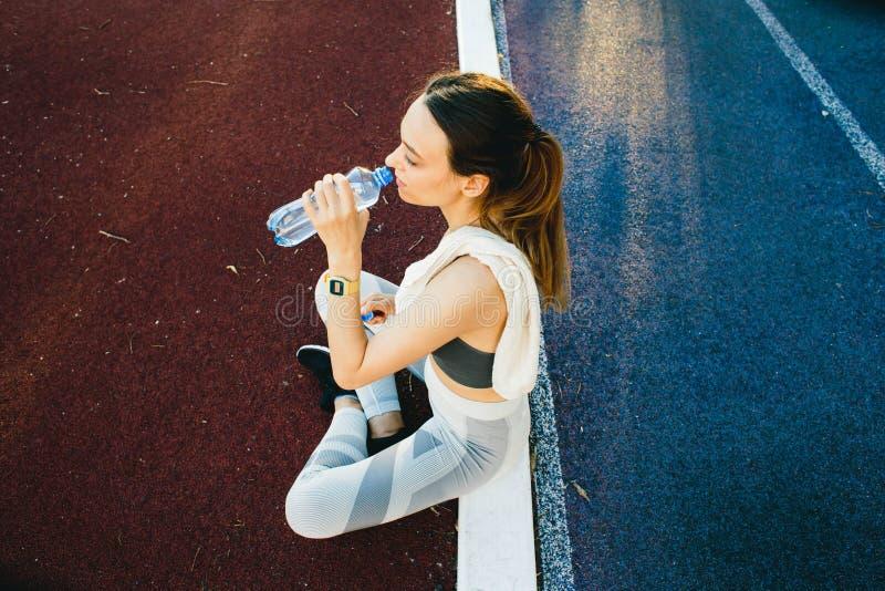 Nätt kvinna som sitter på jordningen med en flaska av vatten efter jogga det fria arkivbilder