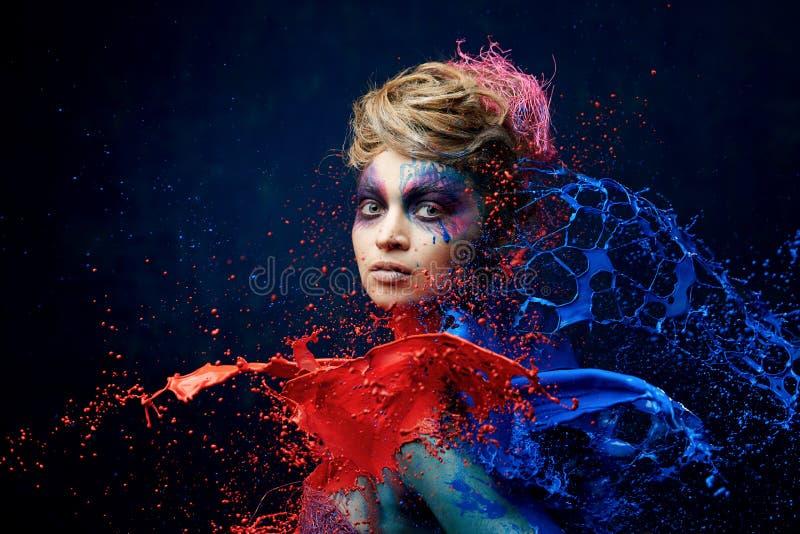 Nätt kvinna som slås av målarfärg royaltyfri foto