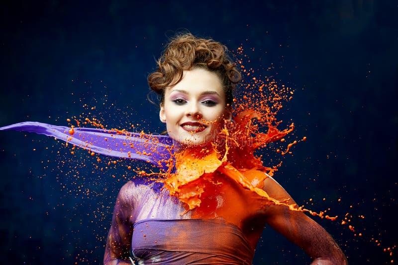 Nätt kvinna som slås av målarfärg royaltyfria foton
