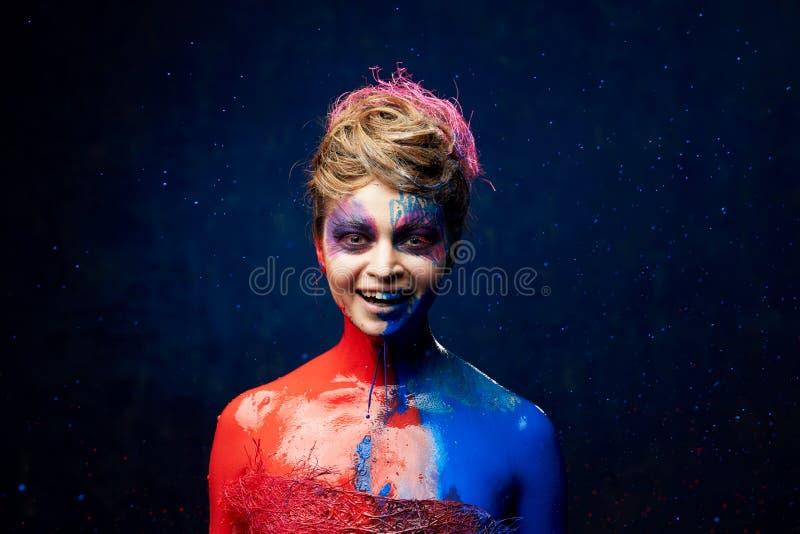 Nätt kvinna som slås av målarfärg royaltyfri bild