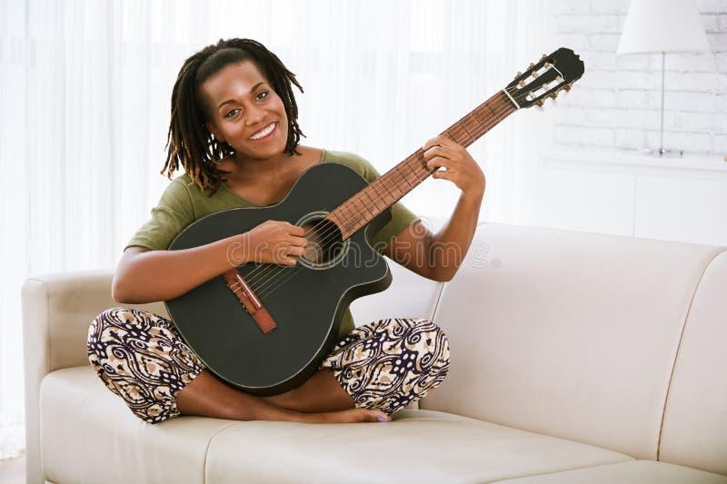 Nätt kvinna som spelar gitarren arkivfoto