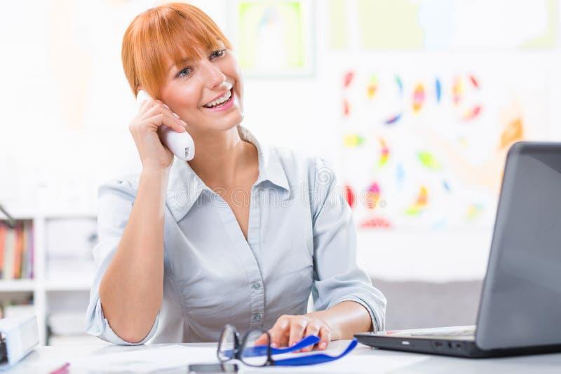 Nätt kvinna som talar på telefonen i kontoret arkivfoto