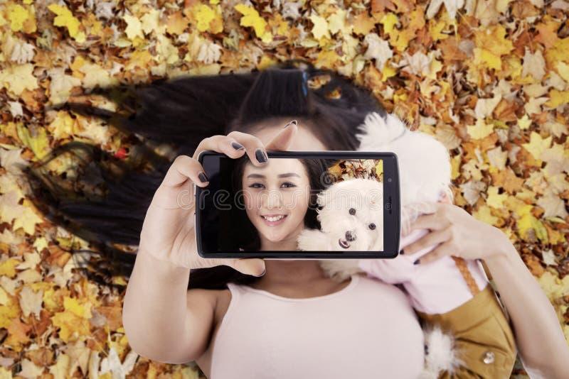 Nätt kvinna som tar bilden med hennes hund royaltyfri foto