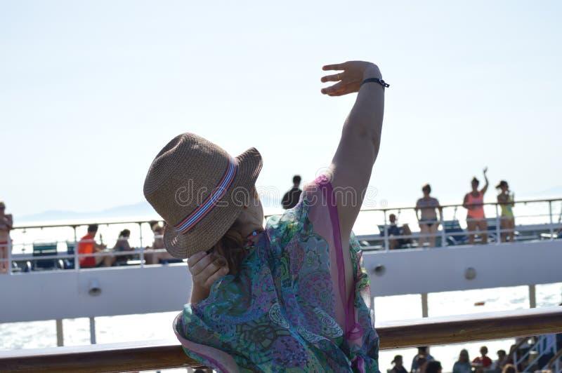 Nätt kvinna som tycker om animeringarna av ett stort kryssningskepp Rekreationkryssninglycka fotografering för bildbyråer