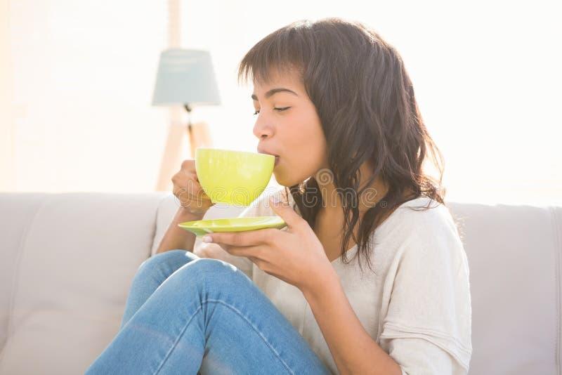Nätt kvinna som tycker om en cappuccino royaltyfri fotografi