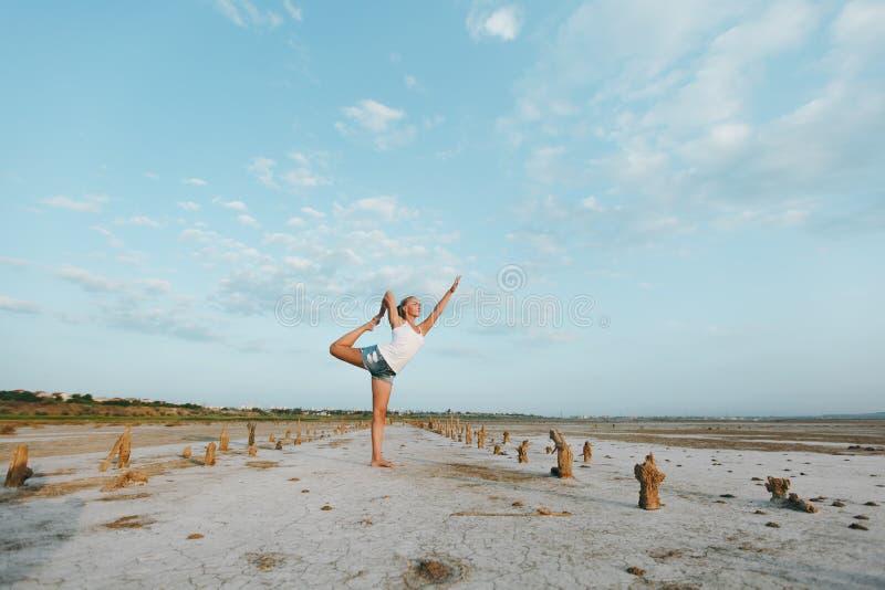 Nätt kvinna som utomhus gör yoga på det jord royaltyfri foto