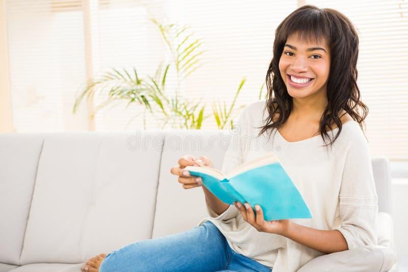 Nätt kvinnaläsning på soffan arkivbild