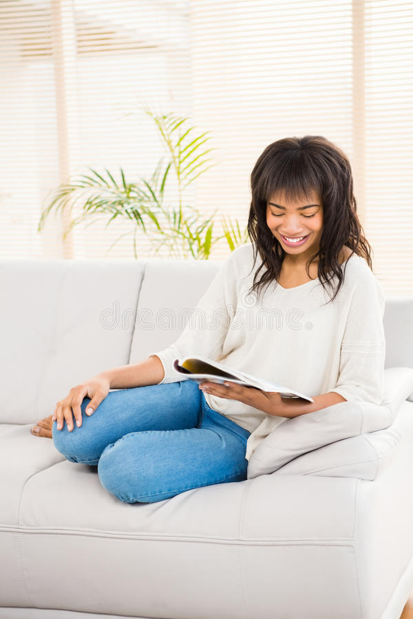 Nätt kvinnaläsning på soffan arkivfoto