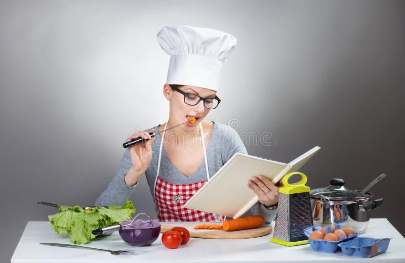 Nätt kvinnamatlagning med kokboken på grå bakgrund arkivfoto